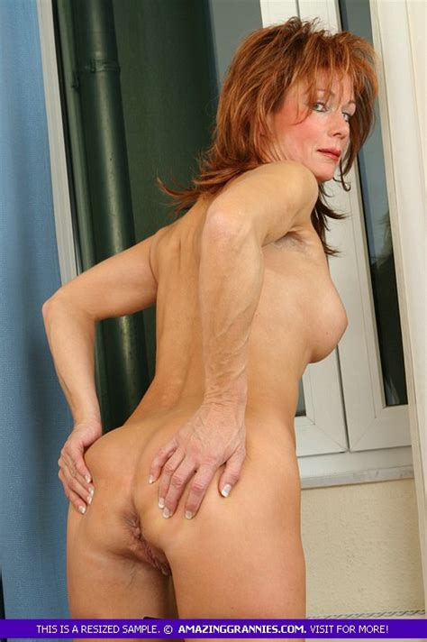 old redhead woman poses all naked in a hotel room with wrinkled sexy body as she spreads her