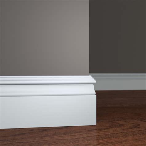 Installing baseboard molding on grey wall and wooden floor
