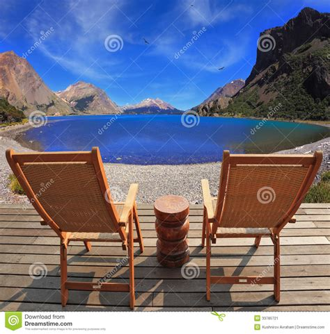 two folding wooden chairs and the mountain lake stock
