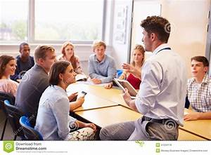 Teacher With College Students Giving Lesson In Classroom ...