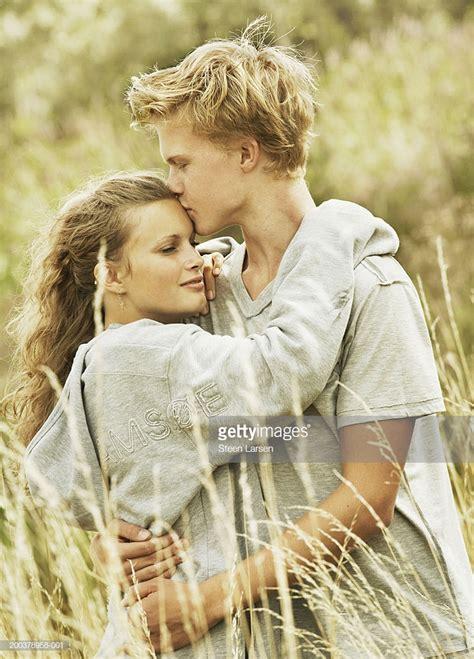 teenage boy kissing girl  embracing  field stock