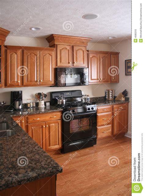 estufa negra de las cabinas de madera de la cocina foto de