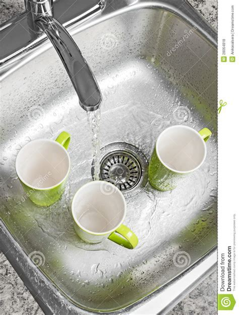 Washing Cups In The Kitchen Sink Royalty Free Stock Photos