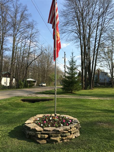 yard flag pole rock ring flower bed around flag pole backyard diy 1204
