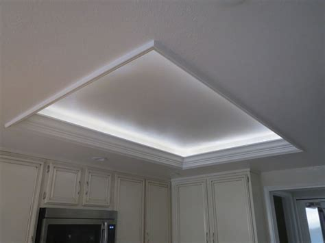 kitchen  white cabinets  stainless steel appliances recessed cove lighting crown molding