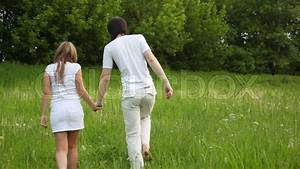 Young man and girl walking away holding hands | Stock ...