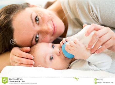 Mom Feeding Baby Boy With A Milk Bottle Stock Image