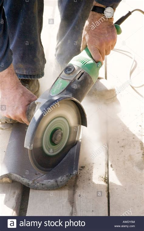 builder cutting roof tiles with an angle grinder stock