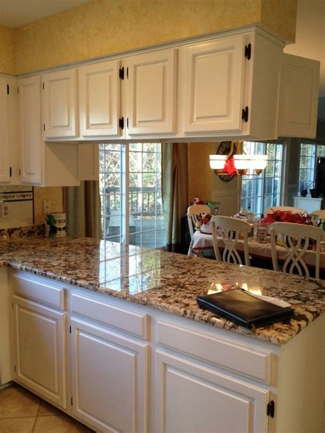 white kitchen cabinets with brown granite countertops