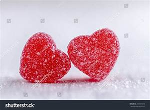 Two cinnamon heart candies coated with sugar sitting on ...