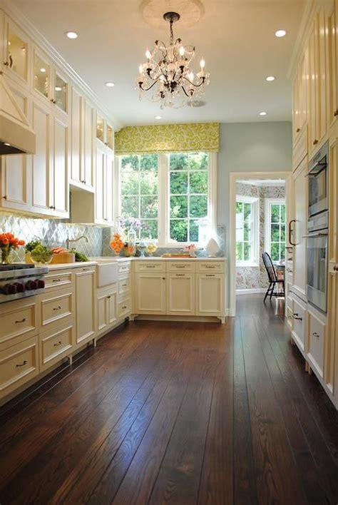 cream cabinets brass hardware green arabesque tile backsplash chandelier hand scraped wood