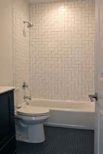 bathroom with herringbone pattern white subway tile surround and black hexagon tile flooring