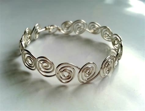 Swirly Wire Bracelet · How To Make A Wire Swirl Bracelet. Colored Stone Rings. Hammered Gold Band. Solar Watches. Womens Black Wedding Rings. Rado Diamond. Spike Stud Earrings. What Is An Anklet Bracelet. Tourmaline Wedding Rings