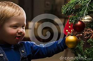 Cute Smiling Boy Decorating A Christmas Tree Stock