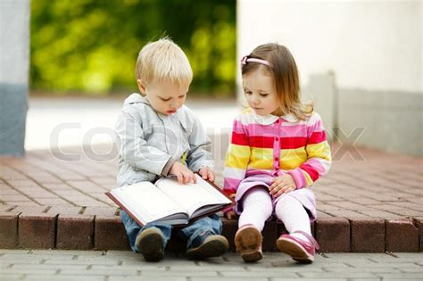 Cute Boy And Girl Reading A Book  Stock Photo Colourbox