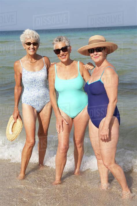 senior women standing  waves  beach stock photo