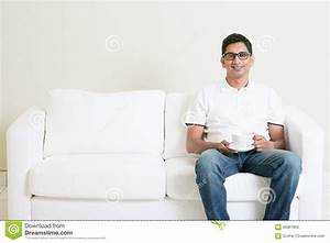 Asian Man Sitting On Couch And Drinking Coffee Stock Photo ...