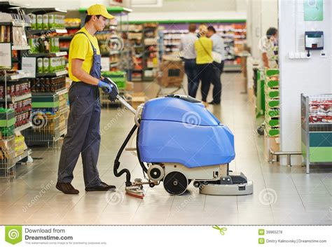 Harga The Shop Clean Free worker cleaning store floor with machine stock photo