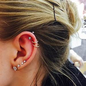 Beautiful ear adorned with four lobe and three helix ...