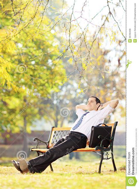 homme d affaires assis sur un banc d 233 tendant en parc images libres de droits image 35765439