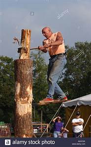 Lumberjack competition man cutting log with axe ax at a ...