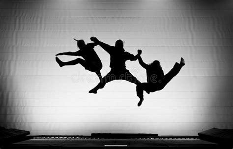 Silhouette Of Gymnasts On Trampoline Stock Photo