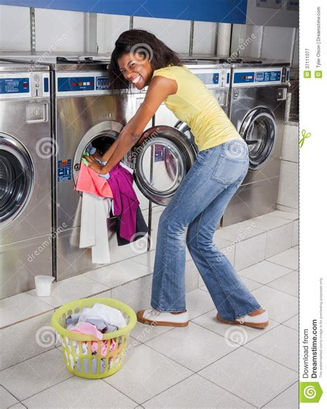 commercial laundry machines pushing clothes in washing machine stock image