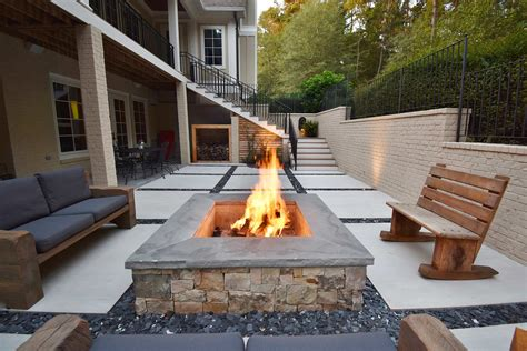 Fire pits are more than just beautiful features for outdoor spaces, they are vehicles for bringing people together. Concrete Squares and Slate Chips Patio with Custom Fire Pit