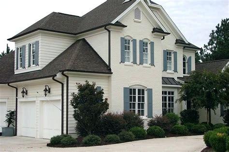 gray house blue shutters bricks brick exterior cream