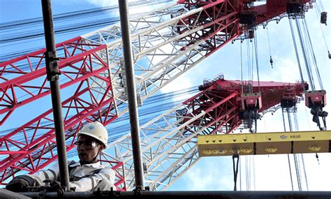 A Cnooc Worker Sets Up Scaffolding At A Construction Site