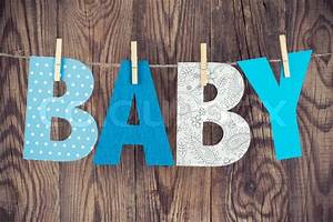 letters of word baby hanging on clothesline against wooden With baby hanging letters