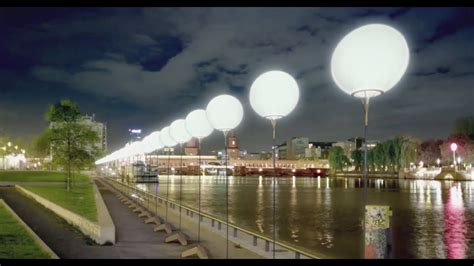 germans celebrate the fall of the berlin wall with lights and balloons