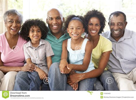 Extended Family Relaxing On Sofa At Home Together Stock