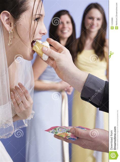 groom feeding  bride  wedding cake stock photo