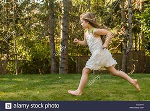 Seven year old girl wearing a sleeveless dress, running ...