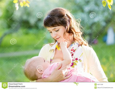 Young Mother Breast Feeding Her Baby Girl Outdoors Stock