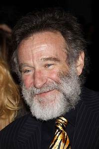 Robin Williams in very close-up, with a large gray beard ...