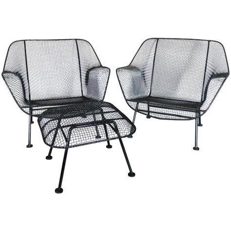 pair of woodard wrought iron with mesh lounge chairs for