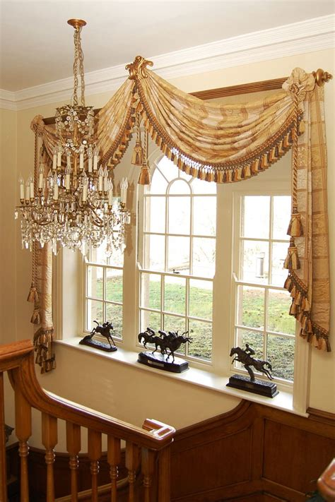 Drapery Swags by One Large Fringed Scarf Draped On Each Corner Of A Wooden