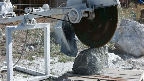jade rock being cut on a table with a slab saw to