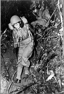 """""""Two United States Army nurses carry heavy combat packs on ..."""