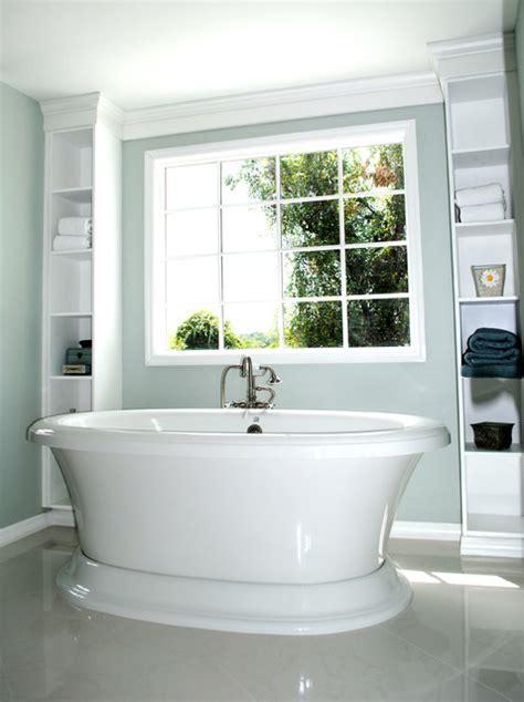 bath featuring freestanding tub framed  built  shelves
