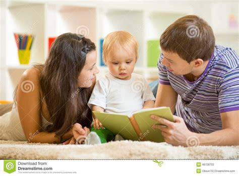 Young Parents Mom And Dad Reading Children Book To Stock