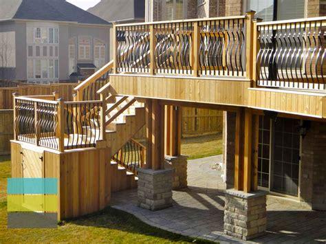 level cedar deck  wrought iron railings pergola  stone walkout basement