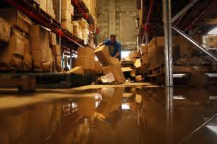 a man sorts through damaged merchandise in a flood hit warehouse in brisbane abc news