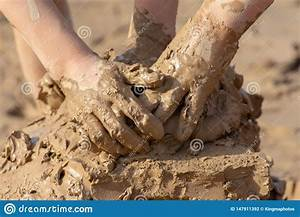 Child S Hand In Clay Mud Mixing Around Outside On A Sunny