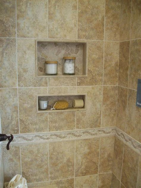 A Ceramic Tile Shower With 2 Inset Shelves In A Bathroom
