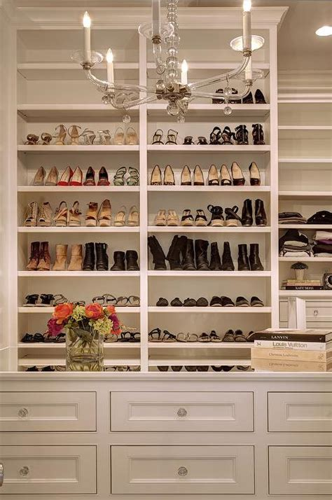 built in shoe rack mirrored top closet island with glass chandelier
