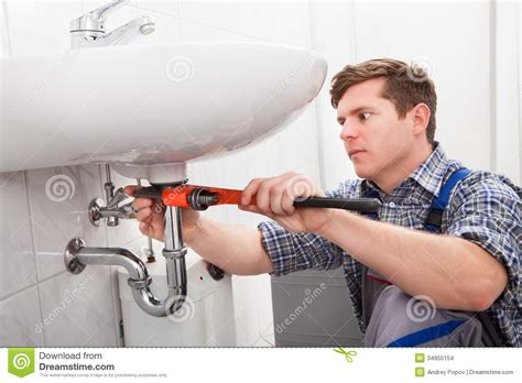 fix faucet kitchen portrait of plumber fixing a sink stock photo image