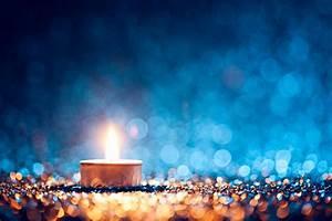 lighted candle on defocused blue background tea